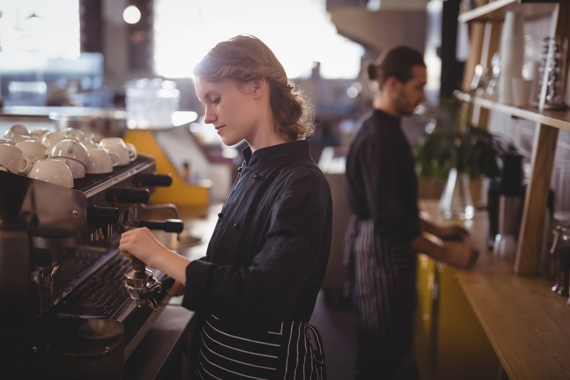 Side view of young baristas
