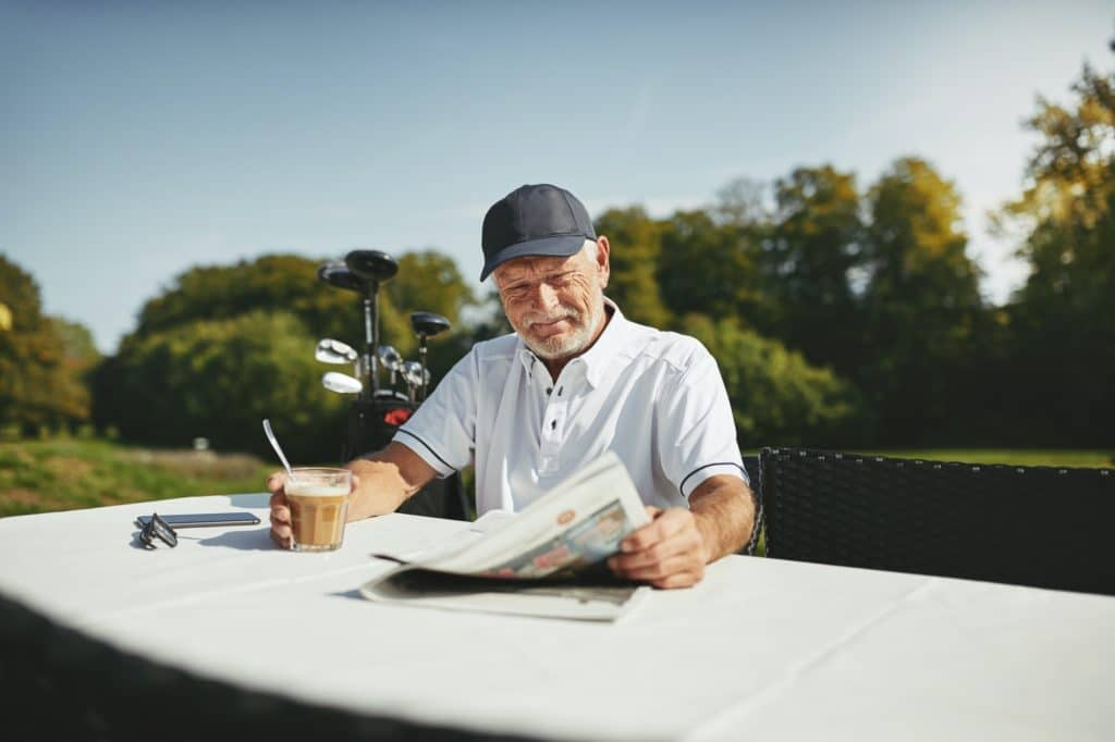 Smiling senior man drinking coffee after a round of golf