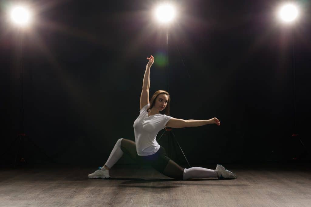 Dance, hip-hop, jazz funk and people concept - flexible young woman dancing in the darkness under
