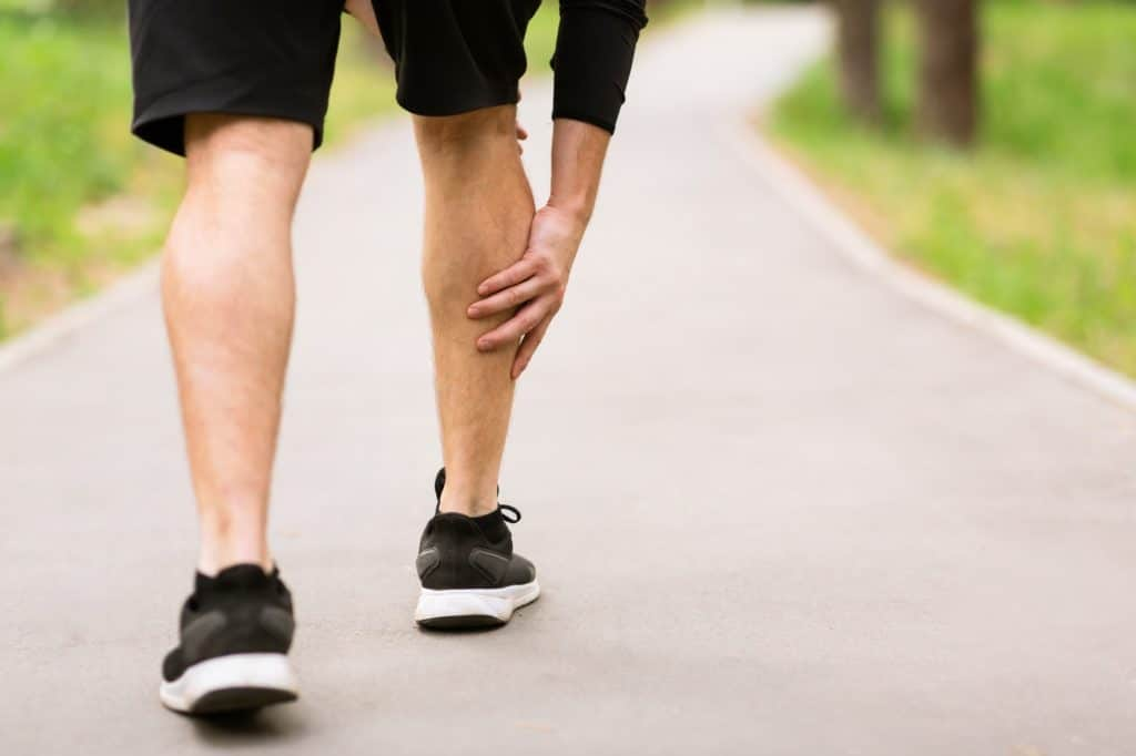 Calf sport muscle injury. Runner with muscle pain in leg
