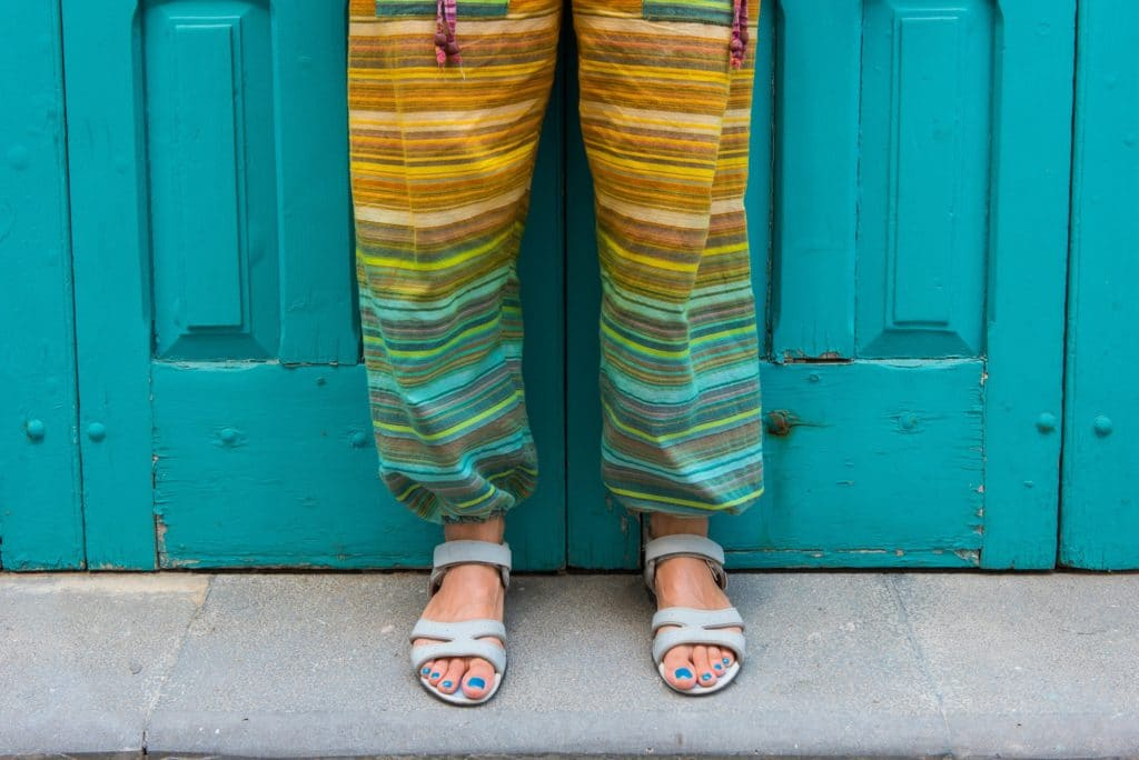 Feet of a woman in sandals with blue toe nails. Colorful hippie pants. Detail