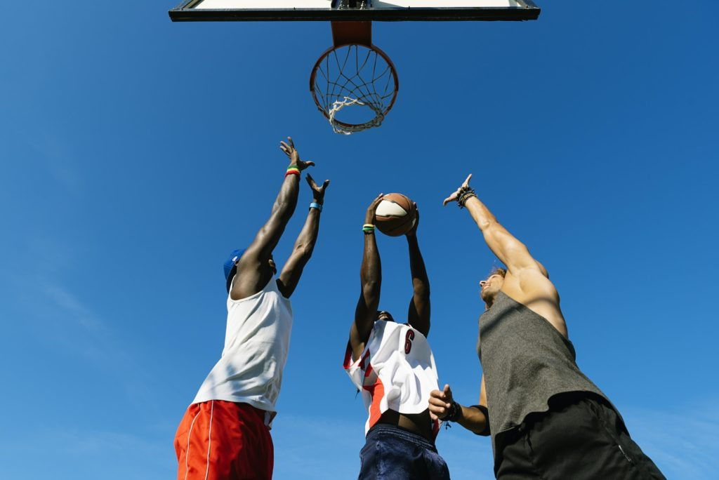 Friends playing basketball in court.