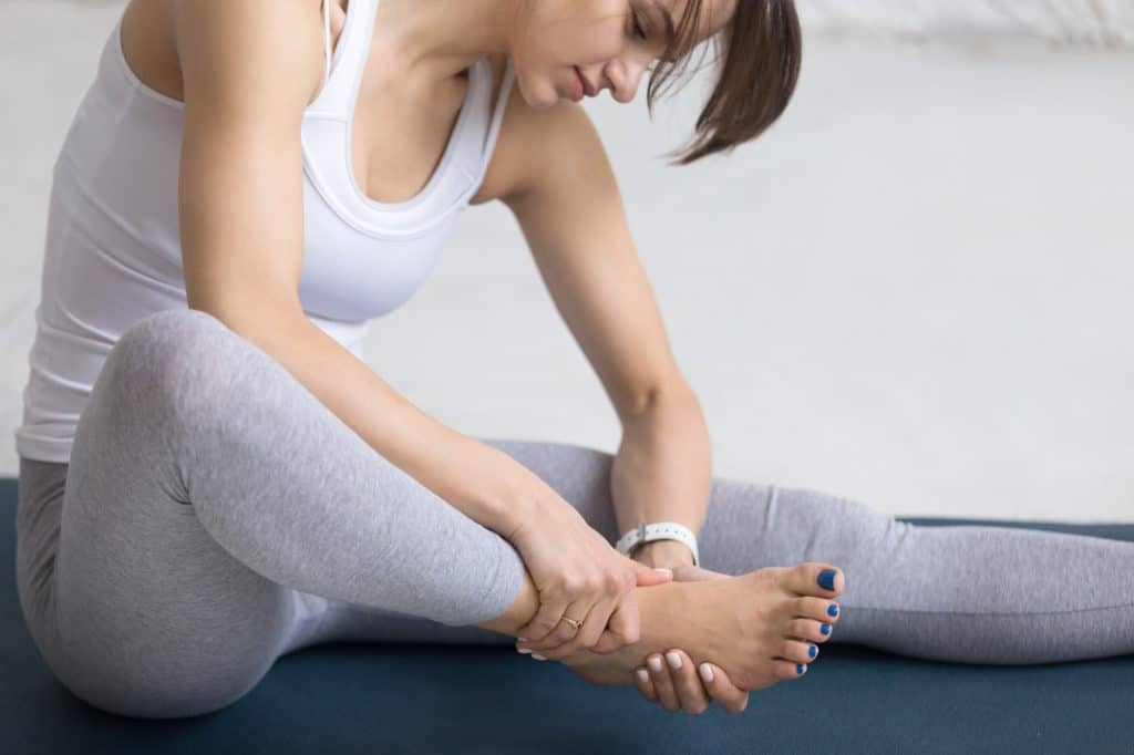 Woman massaging her foot during sport practice