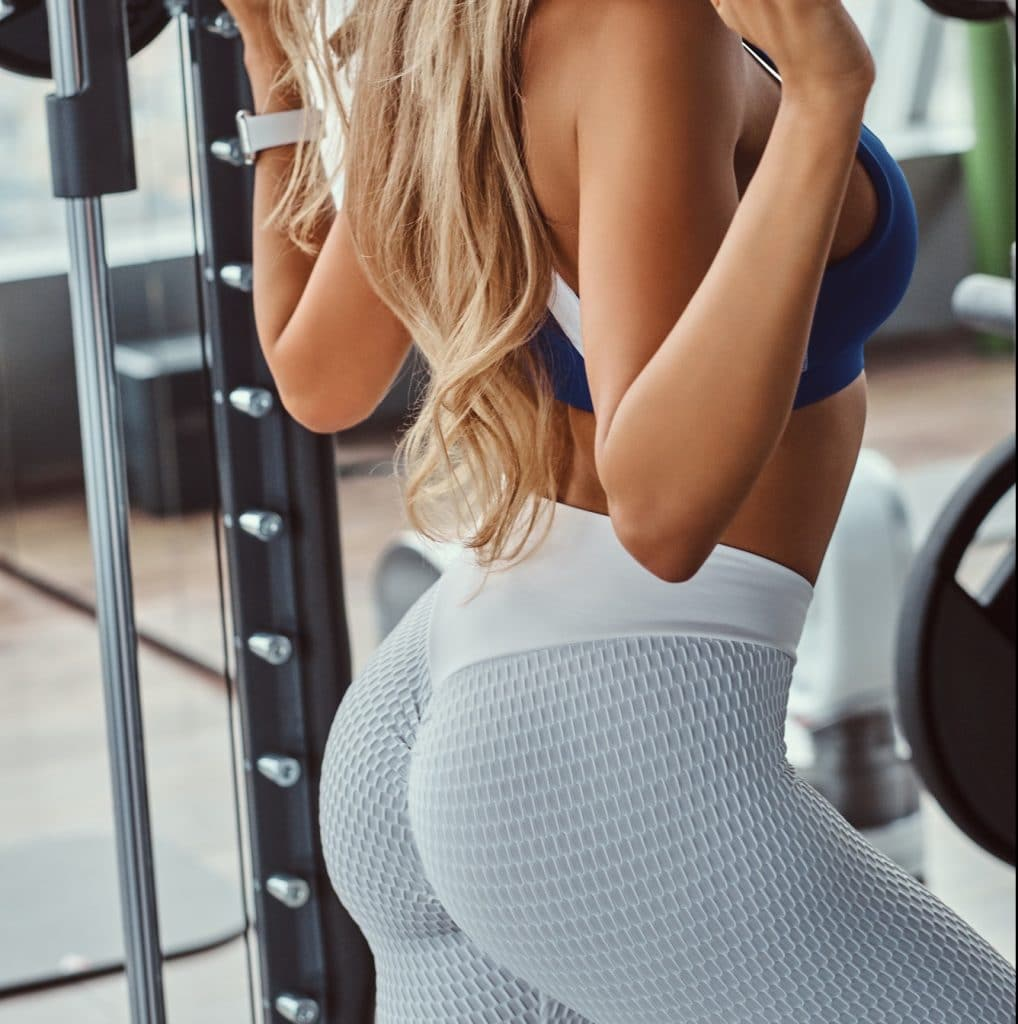 Beautiful fitness girl doing squats on smith machine at the gym.
