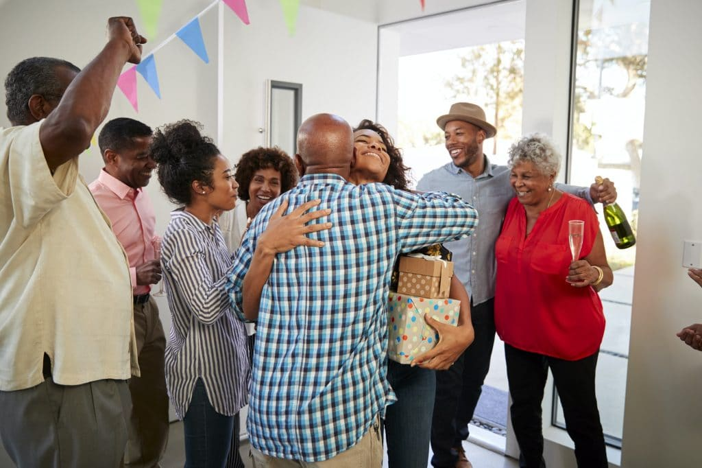 Black grandparents welcoming guests to their house for a family party