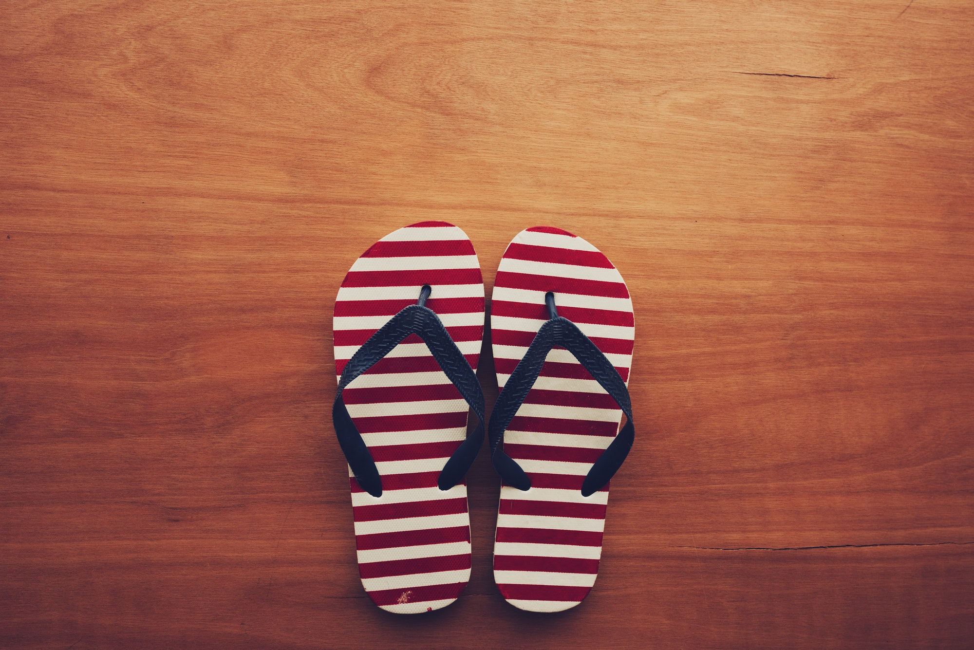 Beach sandals flip flops on wooden background