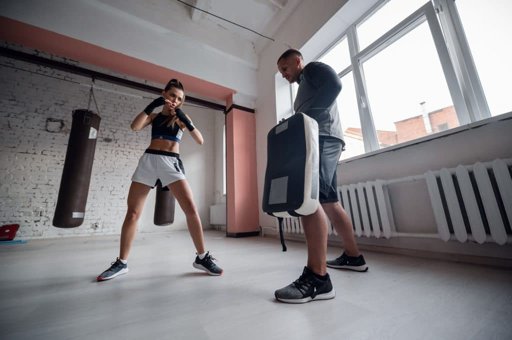 Training fight of male and female kickboxers. Practicing kicks and strikes on the boxing paw