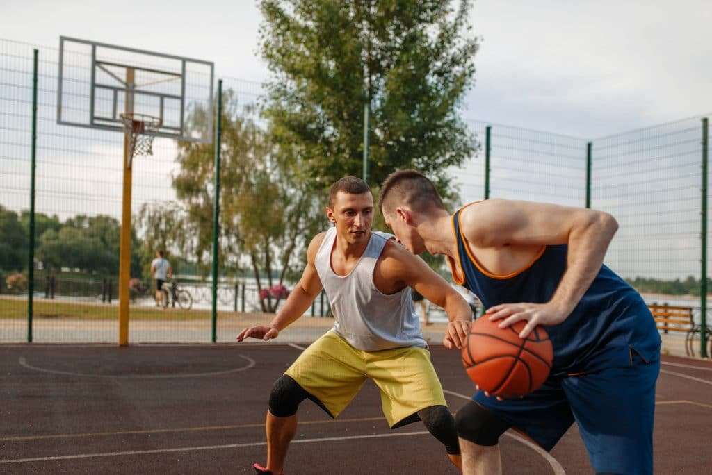 Basketball players playing intense match outdoor