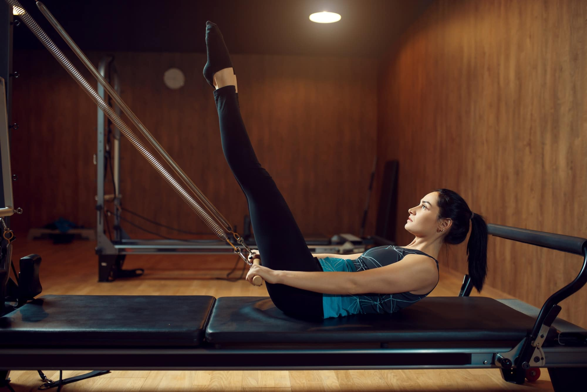 Sporty woman doing pilates exercise in gym
