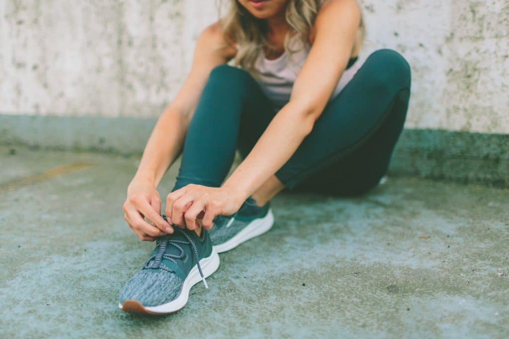 A young woman tying her running shoes.