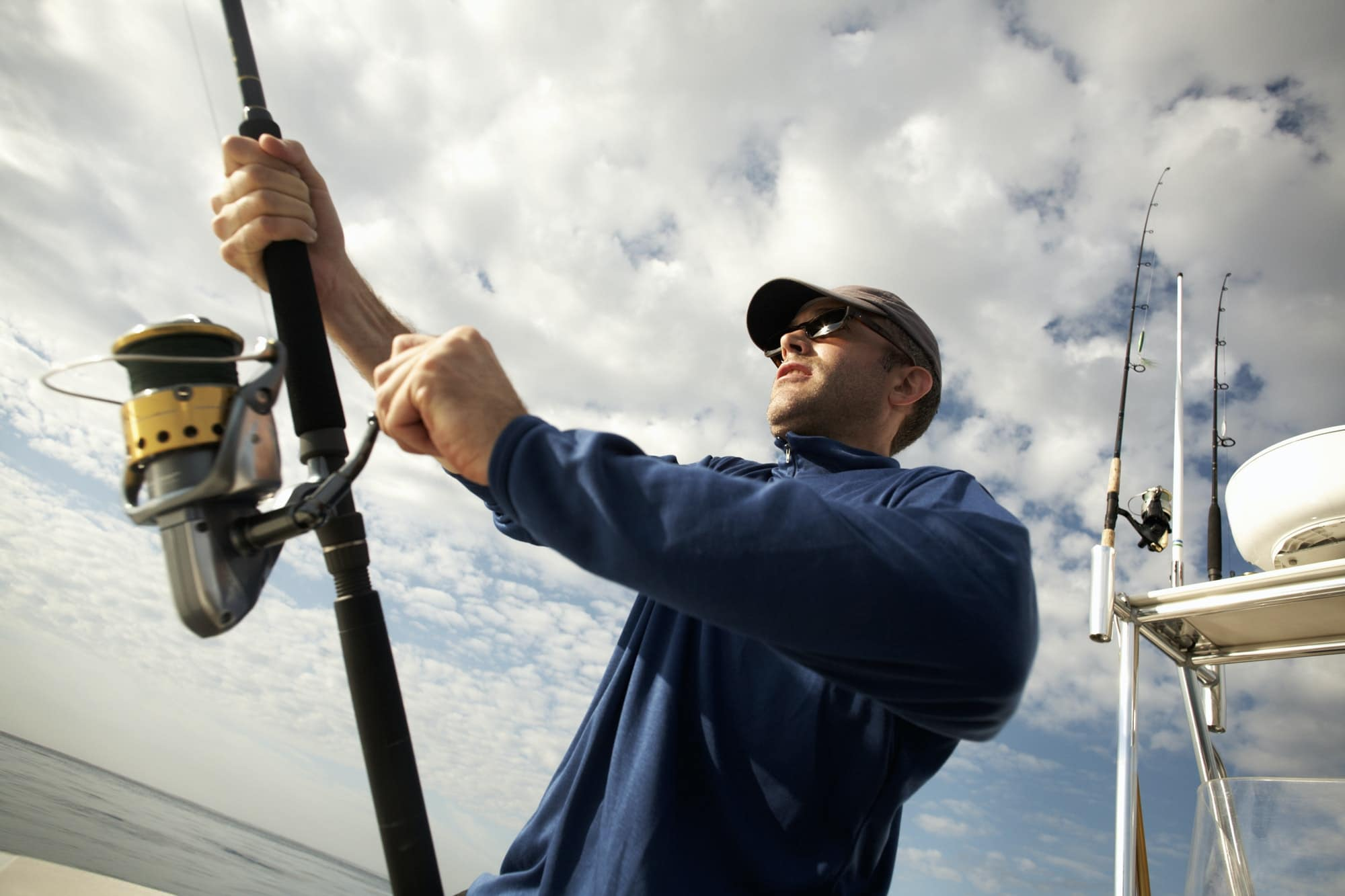 A man on a boat holding a fishing rod.