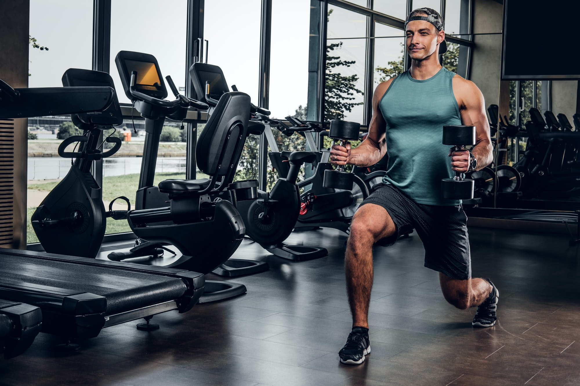 Man has training with dumbbells at gym