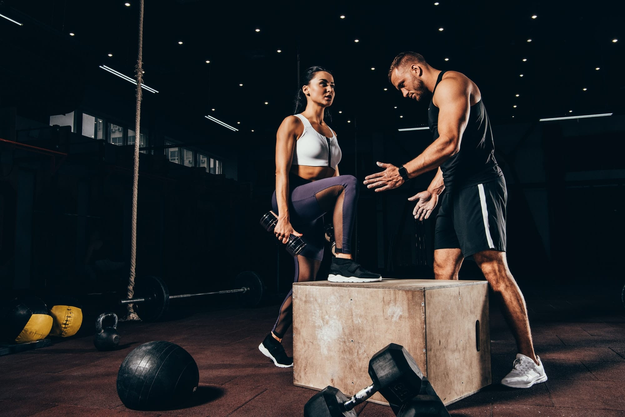 fit woman exercising with trainer on cube in dark gym
