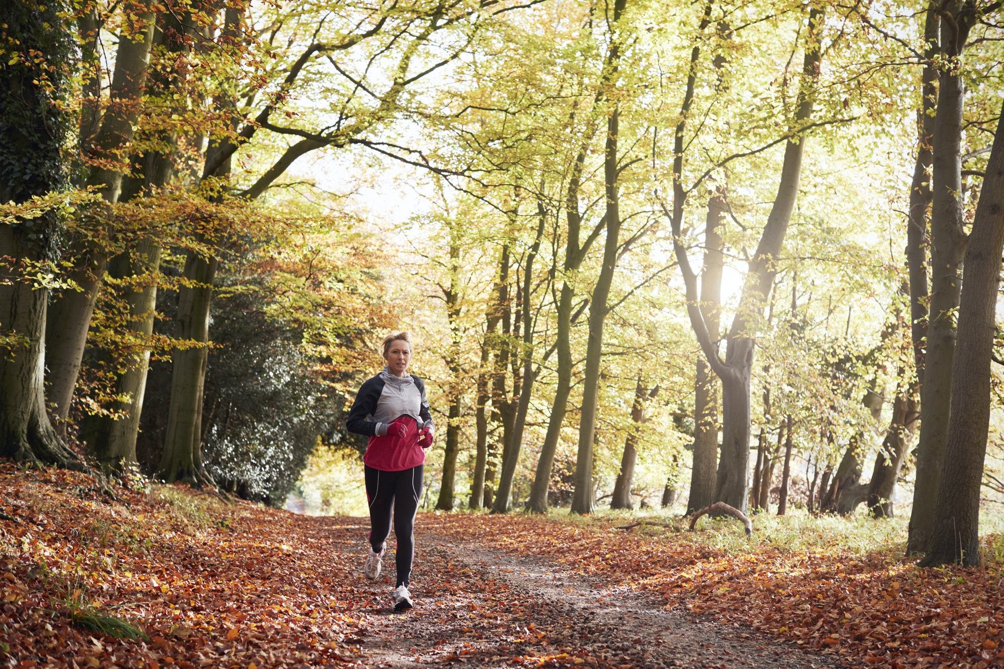 Mature Woman Running Through Autumn Woodland
