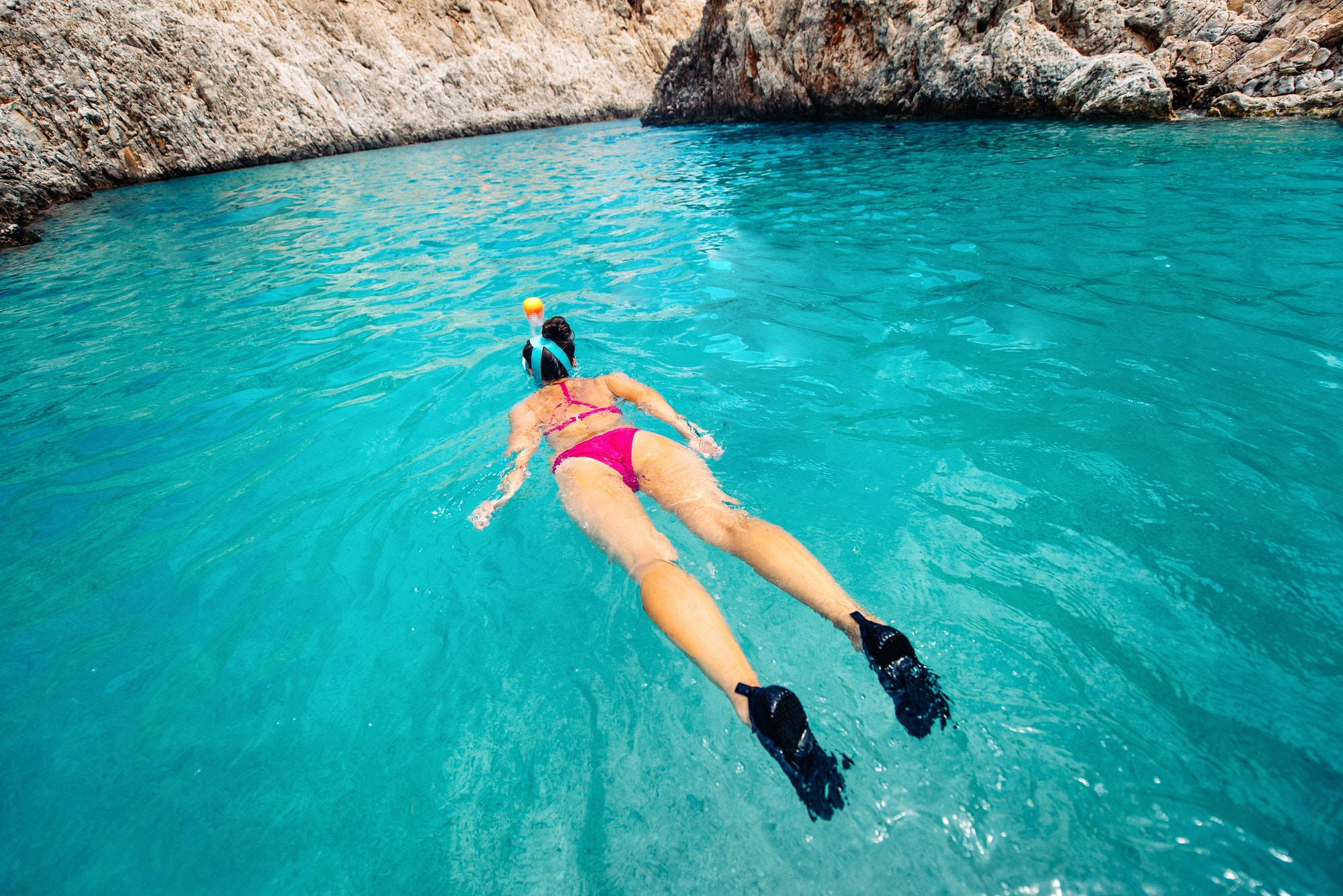 Snorkeling details, woman looking for coral reef in tropical island
