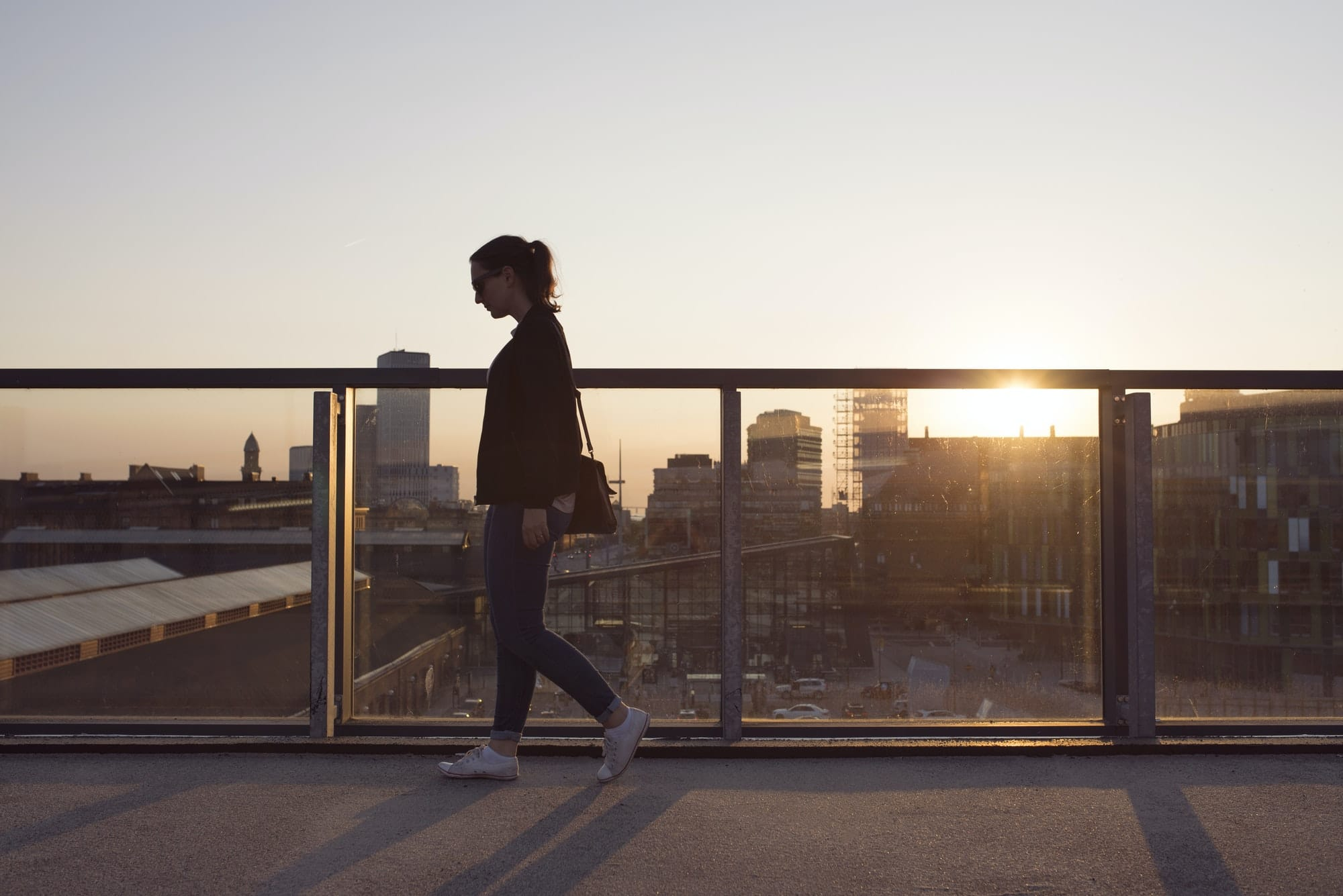 Woman walking on elevated walkway at sunset