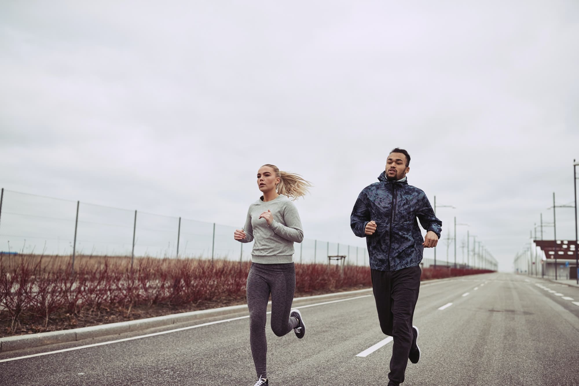 Diverse young couple running along a country road