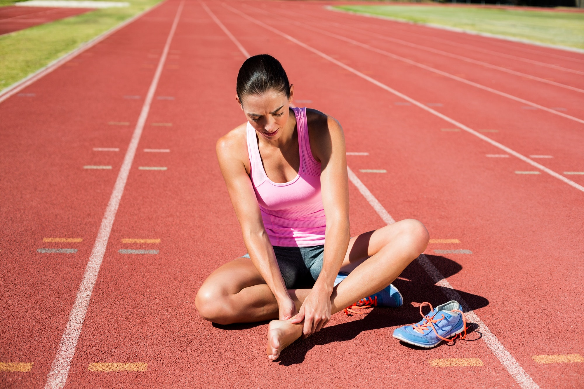 Female athlete with foot pain on running track