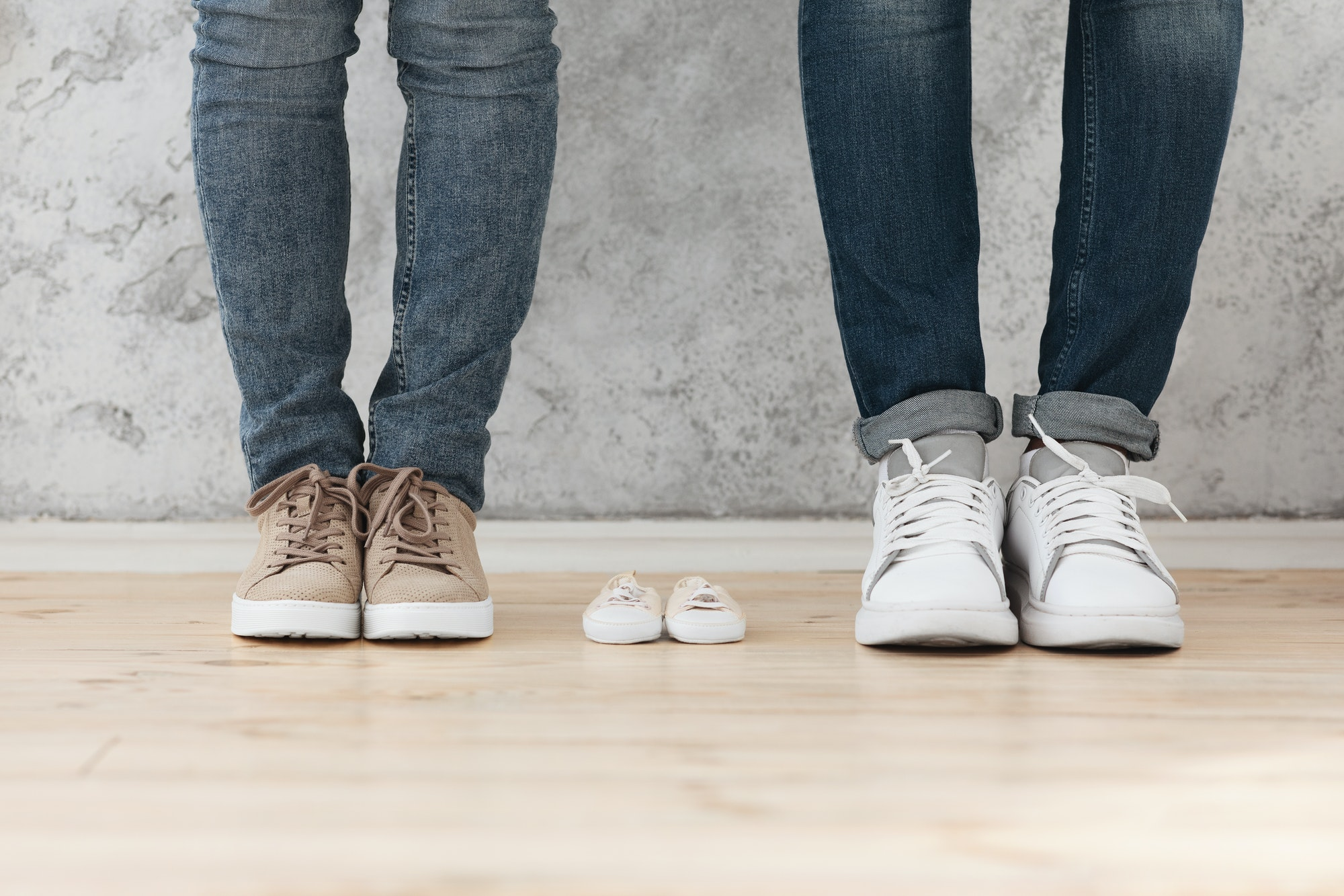 Man and woman standing next to small baby shoes